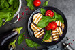 Grilled eggplant with fresh tomatoes and spinach leaves