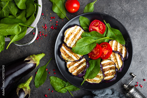 Wall mural Grilled eggplant with fresh tomatoes and spinach leaves