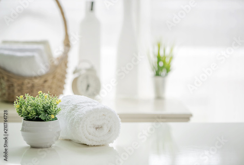 Roll up of white towels on white table with copy space on blurred living room background © coolhand1180