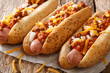Authentic chili hot dog with cheddar cheese, onion and spicy sauce close-up on paper. horizontal