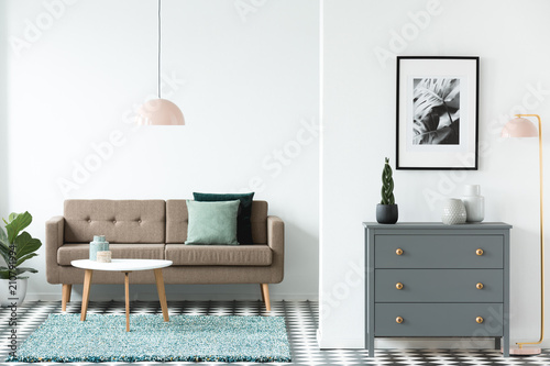 Brown sofa with green cushions standing in white open space living room interior with wooden table on carpet, grey cupboard, simple poster and pastel pink lamps