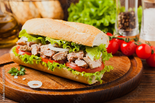 Fototapeta Delicious tuna sandwich, served with lettuce, tomato and onion.