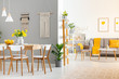 Leinwanddruck Bild - Real photo of a spacious home interior with wooden table, white chairs and macrame on the wall in dining room and a gray sofa and armchair in the living room