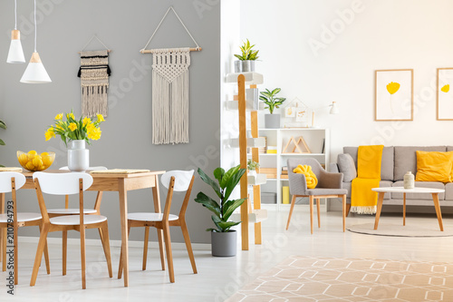 Leinwanddruck Bild Real photo of a spacious home interior with wooden table, white chairs and macrame on the wall in dining room and a gray sofa and armchair in the living room