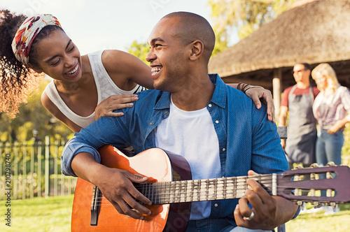 Fotobehang Muziek Happy man playing guitar outdoor
