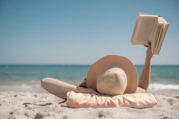 Frau am Strand liest Buch