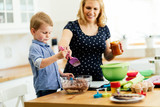 Smart cute child helping mother in kitchen - 210802587