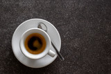 Small italian espresso in white ceramic cup with spoon isolated on dark granite desk from above. Space for text. - 210805707