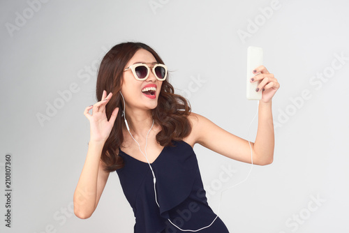 Happy carefree young woman dancing and listening to music from smartphone over grey background - 210807360
