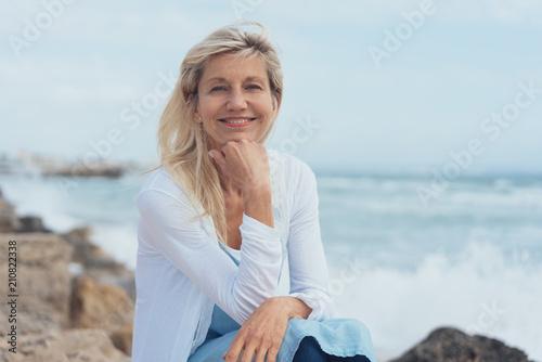 Foto Murales glückliche best-agerin sitzt am meer und entspannt