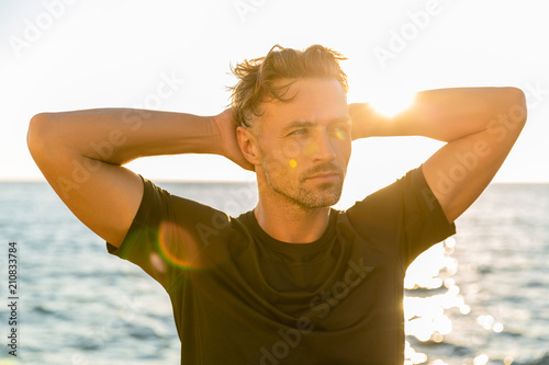 adult sportsman on seashore in front of sunrise