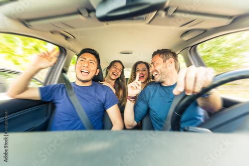 Fototapeta Friends inside the car singing during a road trip