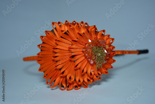 Aluminium Gerbera A beautiful ornament of an orange thin ribbon with stones and a metal chain in the form and in the style of a peacock