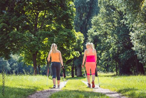 Leinwanddruck Bild Mutter und Tochter beim Nordic Walking für bessere Fitness