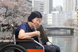 Senior asian woman sleepy while reading magazine in park