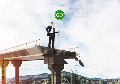 Young businessman holding street safety sign. - 210887311
