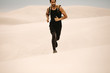 Leinwanddruck Bild - Man running on sand dunes