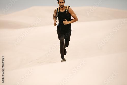 Leinwanddruck Bild Man running on sand dunes