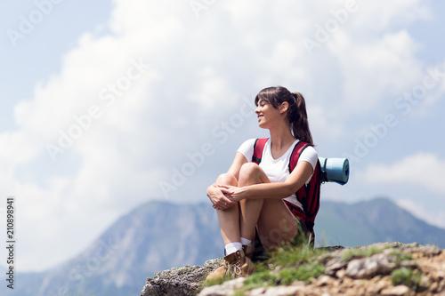 Fototapeta Successful female hiker enjoy the view hiking on mountain peak