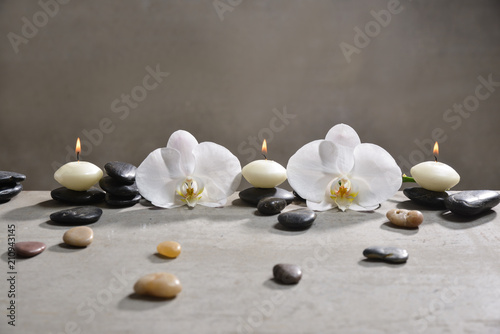 Aluminium Spa Three candle with pile of black stones and white orchid on gray background