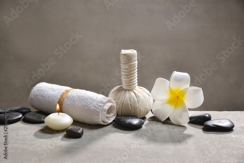Aluminium Spa candle with pile of black stones and white frangipani, herbal ball.towel on gray background