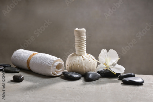 Aluminium Spa pile of black stones and white orchid, herbal ball.towel on gray background