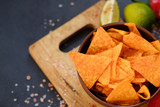 homemade fried tortilla nacho chips. spicy crisps in a bowl on dark background. delicious salty food snack - 210948343