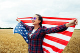 Young beautiful woman holding USA flag - 210949917