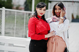 Two fashionable arabian girls friends posed outdoor. Stylish muslim womans.