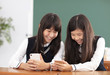 teenager girl student watching the smart phone in classroom
