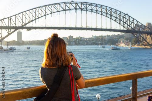 Leinwanddruck Bild Female tourist with backpack bag  taking photos of Sydney Harbour Bridge during summer vacation trip.