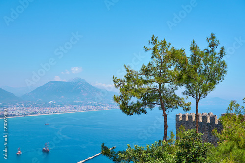 Fotobehang Blauw Seaside of Analya, Turkey with mountains on a background and wall of ancient castle.