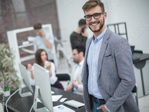 modern young businessman on the background of the workplace - 210980956