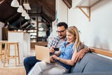 Couple shopping online while sitting on the sofa in modern apartment. - 210984122