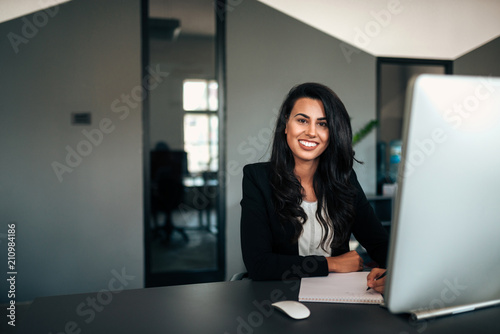Portrait of successful businesswoman writing in notepad. - 210984186