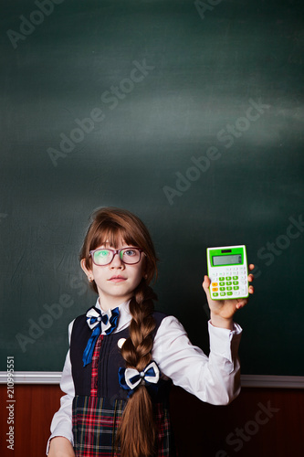 girl in glasses and school uniform, in a classroom on a background of a chalkboard with a calculator - 210995551