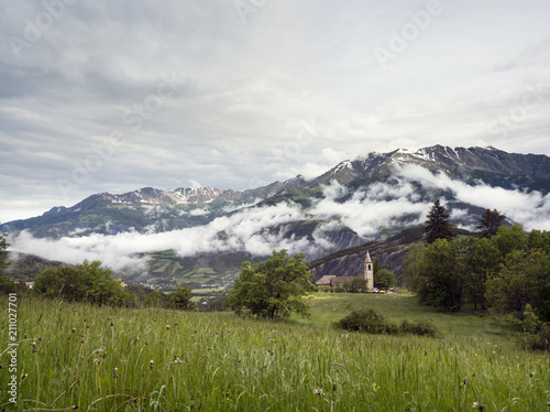 mountains with snow of national park mercantour and church near barcelonnette in alpes de provence.
