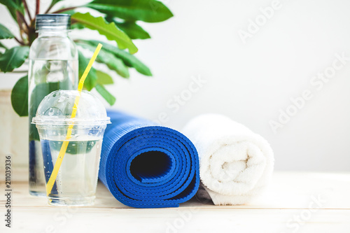 set for sports, blue yoga mat towel and a bottle of water on a light background The concept of a healthy lifestyle. Copy space © Natalya