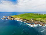 Spectacular aerial view of Mullaghmore Head with huge waves rolling ashore. Picturesque scenery with magnificent Classiebawn Castle.