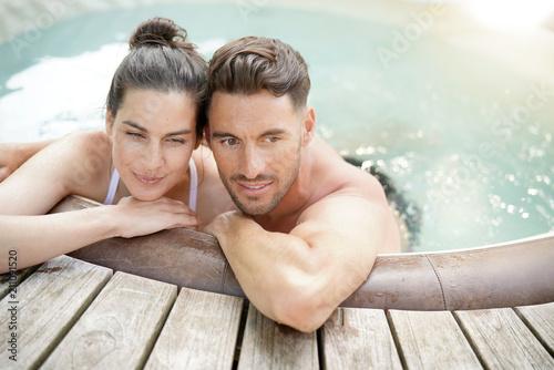 Leinwanddruck Bild Couple enjoying relaxing time in jacuzzi