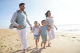 Family running on sandy beach at sunset