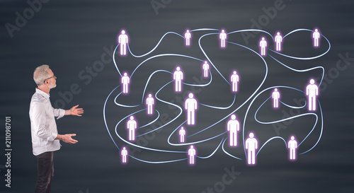 A social network concept explained by a businessman on a wall screen - 211098701