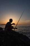 An adult man fishing on the rocks at sunset, on the seashore in Greece - 211100372