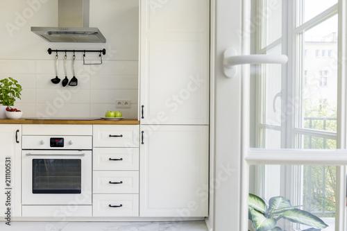 Srebrny okap kuchenny nad drewnianym blatem w białej kuchni z balkonem. Prawdziwe zdjęcie