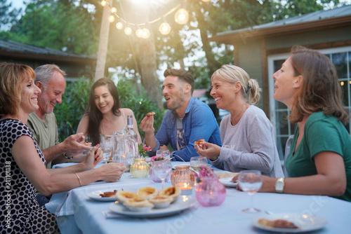 Przyjaciele cieszą się letni obiad z grilla w ogrodzie
