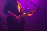 Guitarist plays on guitar in purple lights - 211101776