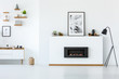 Black lamp next to fireplace under posters in minimal white living room interior. Real photo