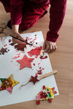 Young child painting Christmas decorations kneeling down on the floor - 211125168