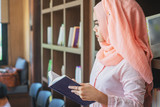 Muslim woman reading book at the library. - 211125384