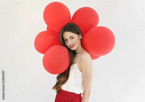 attractive young woman with red balloons on white background